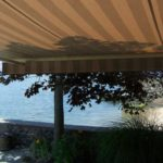 Awning providing shade outdoors with view of sea in the background.