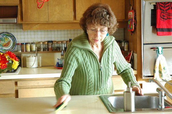 Woman cleaning her countertop with a sponge.