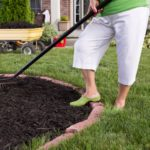 Woman working in her yard spreading mulch in a circle.