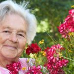 Elderly woman standing outside next to dark pink flowers.
