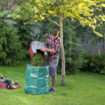 Young man mowing the lawn and pouring the cuttings into a green barrel.