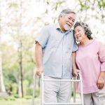 Older couple walking outside with a walker.