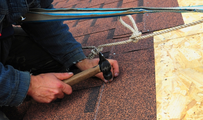 Worker installing shingles on a roof.